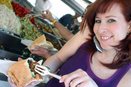 Eating Falafel, while talking on the mobile phone.
