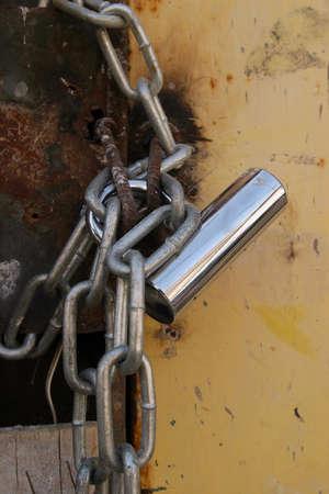 Un candado y una cadena en una antigua puerta.