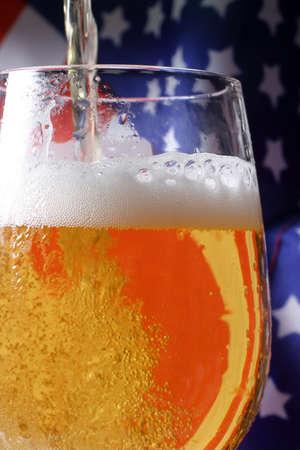 Cerveza fr�a macro y la bandera americana. Foto de archivo
