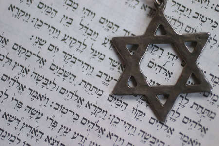 Star of David over the first page of the old testament in Hebrew. The word in the center of the star is Reklamní fotografie