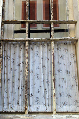 Old window with a floral curtain