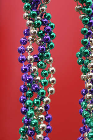 Mardi Gras beads over red Stock Photo