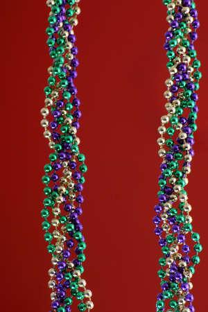 Mardi Gras beads over red Stock Photo