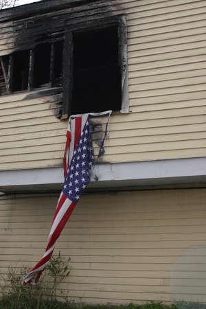 A burnt house and a torn USA flag