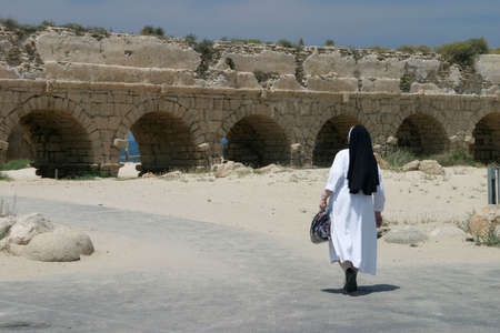 A nun at the aqueduct, Caesarea, Israel