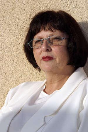 Una mujer de 50 algo mirando a trav�s de las gafas de color azul enmarcada.