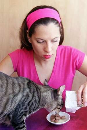 Young woman feeding cat Stock Photo - 918318