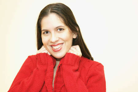 A smiling young woman in a red sweater.