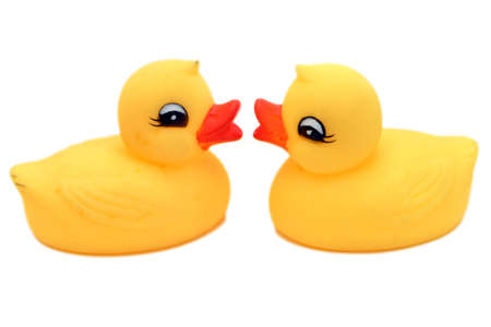 Two yellow bath toy - rubber duck, over white, facing each other. Stock Photo