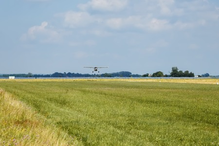 Light aircraft. Light silver airplane lands on airport. Sunny summer day and blue sky with clouds