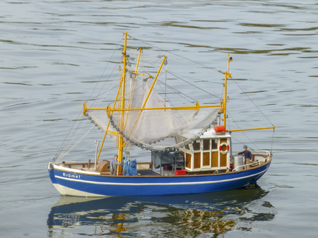 Children's toy of fishing boat is floating on the lake. Ship models. Close up Editorial