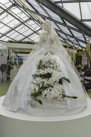 White magnificent dress of bride with live white lilies on a mannequin. Holiday of amazing colors and delicious flavors in NETHERLANDS