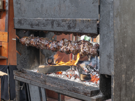 Meat is skewered on a spit, medieval delights. Reconstruction of historical events of the city Magdeburg, Germany. The Kaiser-Otto-Fest. An impressive festival for the whole family