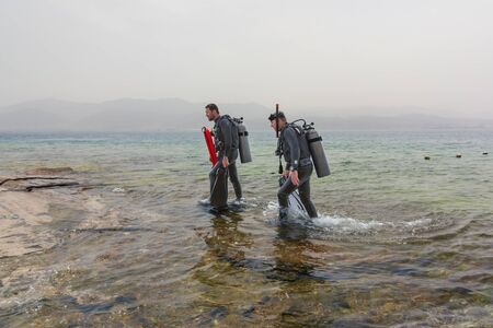 Eilat, Israel - May 2018: School of divers. Two divers go out of the sea. Sport activity Editorial