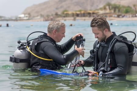 Eilat, Israel - May 2018: School of divers. Men are training in diving. Two divers in basic equipment. A popular water sport and leisure activity