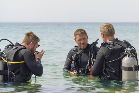 Eilat, Israel - May 2018: School of divers. Men are training in diving. Coach gives an explanation. A popular water sport and leisure activity