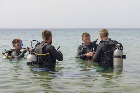 Eilat, Israel - May 2018: Scuba diving course. Men with breathing apparatus in sea. A popular water sport and leisure activity