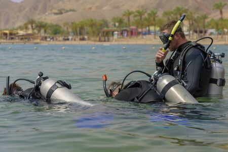 Eilat, Israel - May 2018: Scuba diving course. Men with breathing apparatus are diving into sea. Sport activity vacation. A popular water sport and leisure activity Editorial