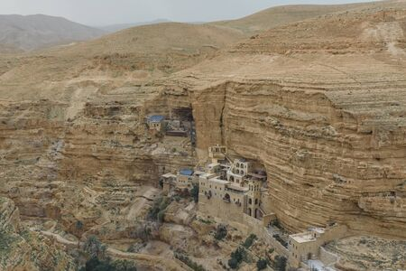 Monastery of Saints George and John Jacob of Choziba is Wadi Qelt, Israel. The cliff-hanging complex with its ancient chapel and gardens, nhabited by Greek Orthodox monks. Landscape. Top view