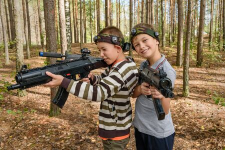 Novgorod, Russia - 04 September 2016: Two boys with laser tag pistols. Laser tag, a game with guns which fire infrared beams. Classmates play together outdoors. Active sport leisure Editorial