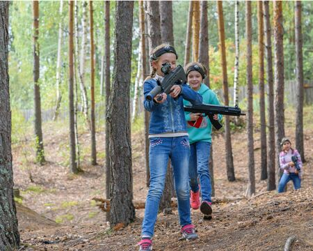 Novgorod, Russia - 04 September 2016: Gilrs with laser tag pistol which fire infrared beams. Classmates play together outdoors. Active sport leisure
