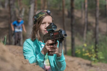 Novgorod, Russia - 04 September 2016: Girl looking into the optical sight of laser tag pistol. Laser tag, a game with guns which fire infrared beams. Classmates play together outdoors