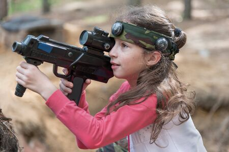 Novgorod, Russia - 04 September 2016: Girl looking into the optical sight of laser tag pistol. Laser tag, a game with guns which fire infrared beams. Classmates play together outdoors. Portrait Editorial