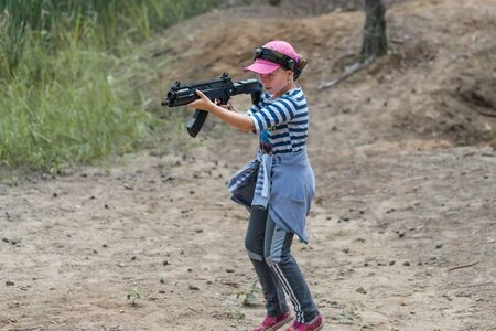 Novgorod, Russia - 04 September 2016: Girl is running and looking into the optical sight of laser tag pistol. Laser tag, a game with guns which fire infrared beams. Classmates play together outdoors