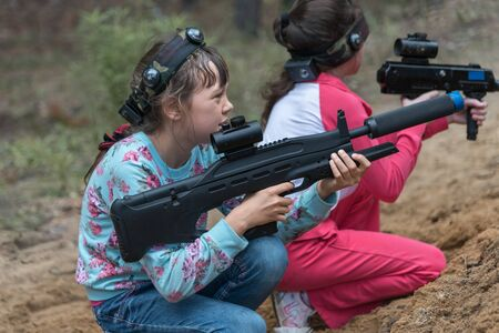 Novgorod, Russia - 04 September 2016: Two girls are sitting in ambush with laser tag pistols. A popular game for wide range of ages. Classmates play together outdoors. Active sport leisure