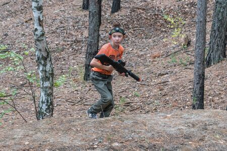 Novgorod, Russia - 04 September 2016: Running boy in forest with a laser tag. Classmates play together outdoors. Active sports amusement