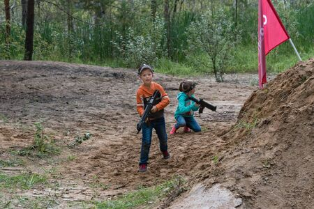 Novgorod, Russia - 04 September 2016: Boy and girl are sitting in ambush with laser tag pistols. Classmates play together outdoors. Active sport amusement