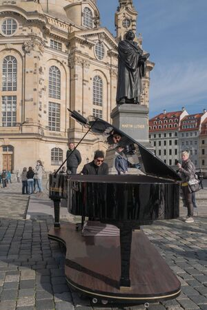 Dresden, Germany - 24 October 2014: Street musician playing piano alone in street on the square in Dresden. Vertical Portrait