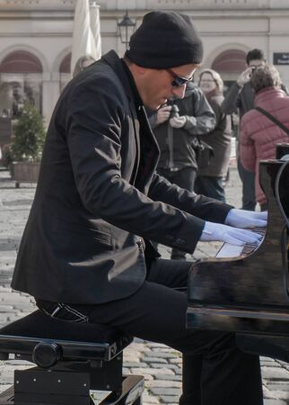 Dresden, Germany - 24 October 2014: Street musician, pianist playing piano alone in street on the square in Dresden. Vertical Portrait