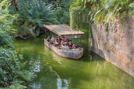 Leipzig, Germany - 25 April 2019: Amusement park. People in boat floating on the river in the tropics. Attraction Landscape