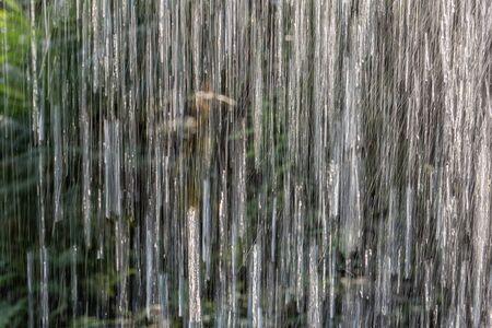 Amusement park. Attraction Tropical rain, water jets. Heavy rain of the tropical rain forest. Landscape background