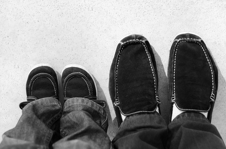 father and son: Shoes on legs of a father and his son Stock Photo