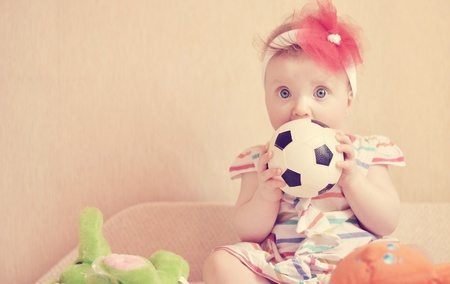 Little girl sitting with a ball on a sofa photo