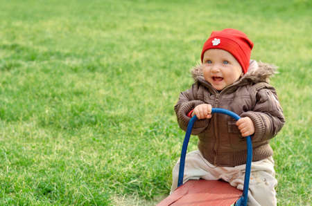 totter: Baby girl sitting on the teeter totter in summer Stock Photo