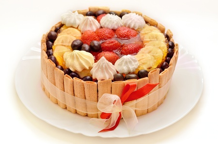 torte: Birthday cake with fruits and red ribbon on white plate