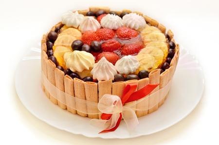 trozo de pastel: Torta de cumplea�os con frutas y una cinta roja en un plato blanco Foto de archivo