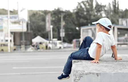 Young preschooler in white t-shirt sitting on a concrete slab in the street photo