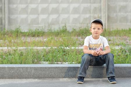 kerb: Stylish preschooler sitting on a road curb outside