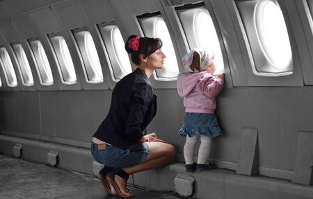 Beautiful mother and infant girl travel in low-cost airplane photo