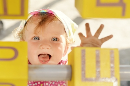 Happy baby girl reaching wooden bricks in the playground Stock Photo - 14754333