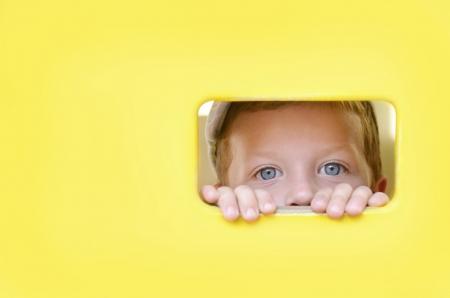 occhi tristi: Ragazzo sveglio che fa capolino attraverso il foro nella parete di legno