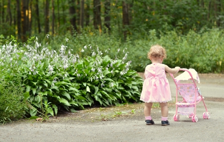 Tender baby girl in pink dress walking with a stroller in the park photo