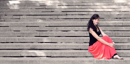 long skirt: Attractive lady in red dress sitting on steps