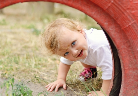 Cute baby girl peeping out of red tire in the playground photo