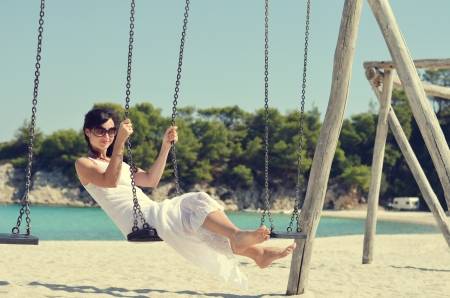 Young smiling lady in white dress swinging on the beach photo