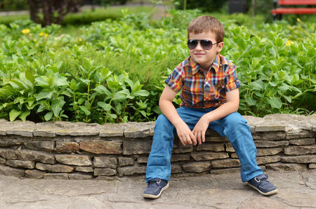 flowers boy: Confident young boy in sunglasses sitting on a retaining wall in summer